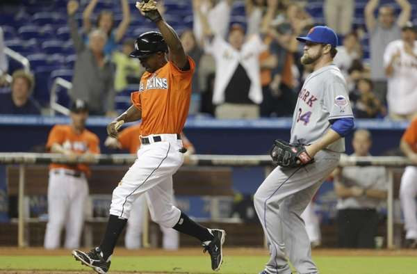 Miami Marlins' Juan Pierre, left, scores the game-winning