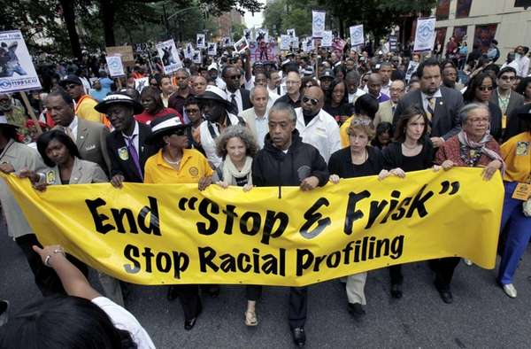 Rev. Al Sharpton, center, walks with thousands along