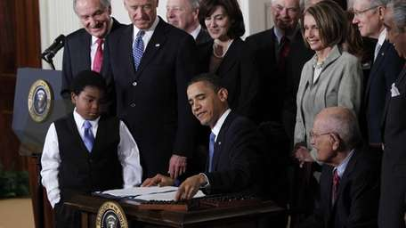 President Barack Obama signs the health care bill