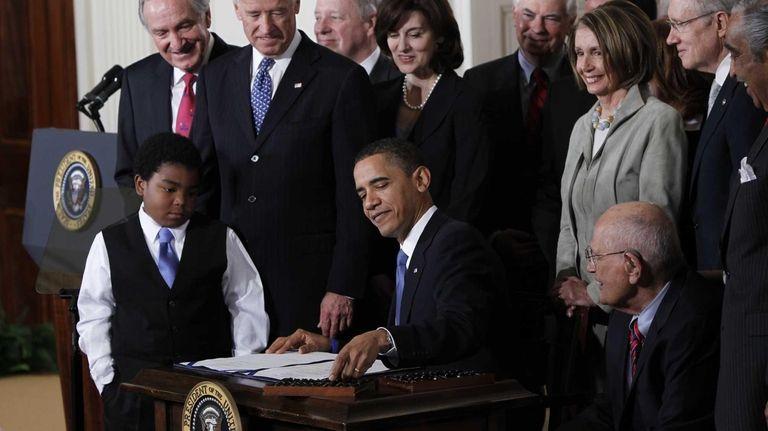 President Barack Obama signs the health care bill