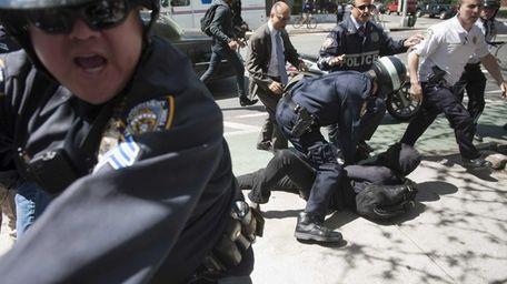 Police arrest demonstrators taking part in an anti-capitalism