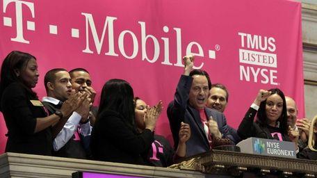 T-Mobile CEO John Legere raises his hand during