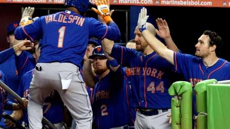 Jordany Valdespin high-fives teammates in the dugout after