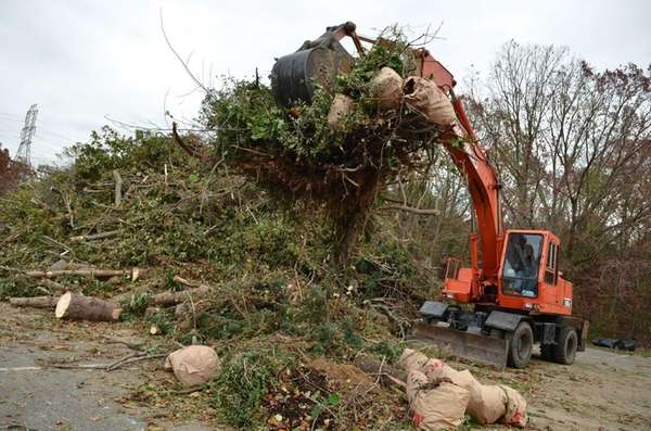 A backhoe piles debris from superstorm Sandy in