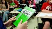 A teacher holds an algebra textbook as she