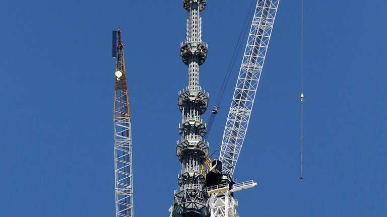 Cranes work adjacent to the spire on top