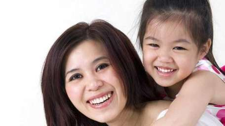 Happy Asian mother giving her daughter a piggyback