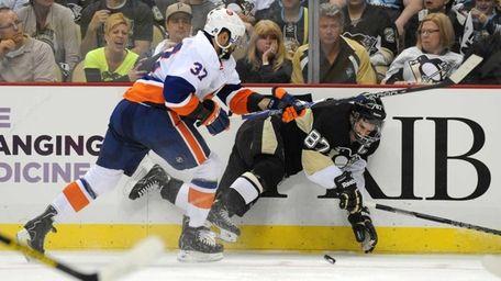 Brian Strait of the Islanders checks Sidney Crosby