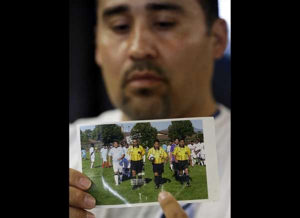 Jose Lopez, points to a undated photo of