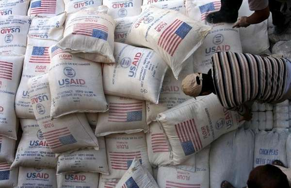 Palestinians unload bags of flour donated by USAID,