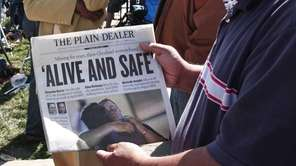 A man shows page one of The Plain