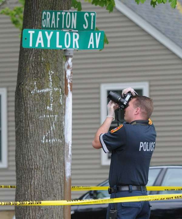 A Suffolk County police investigator photographs a swastika