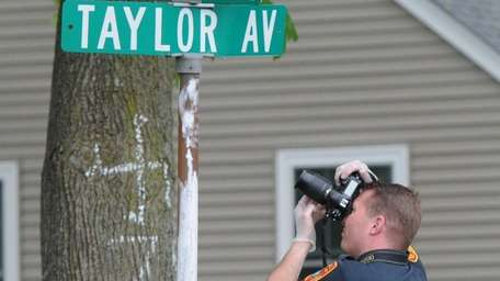 A Suffolk County police investigator photographs a swastika