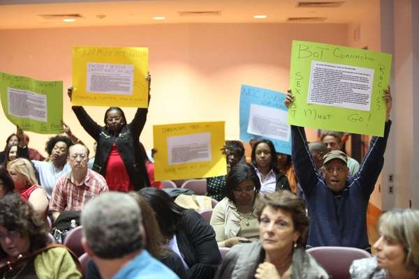 People hold up signs calling for the removal of Anthony Cornachio from the Nassau Community College Board of Trustees for controversial emails during a board of trustees meeting. (May 7, 2013)