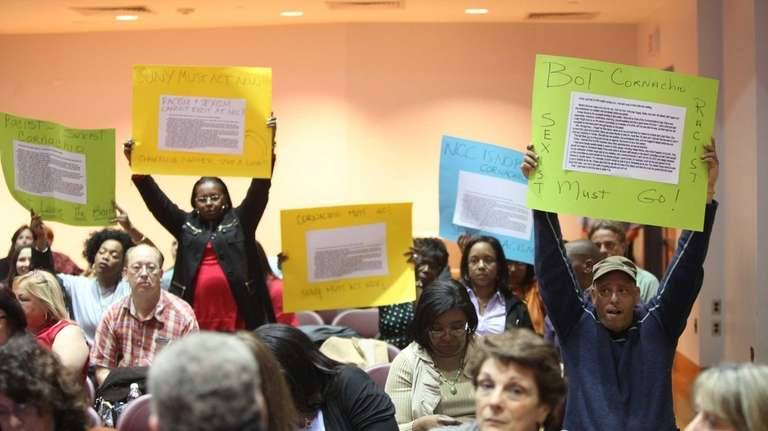 People hold up signs calling for the removal