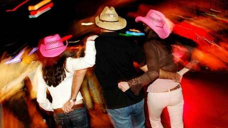 People, dressed in cowboy hats, line dancing to