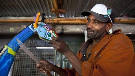 Jackson Mbatha, 40, uses a knife to carve