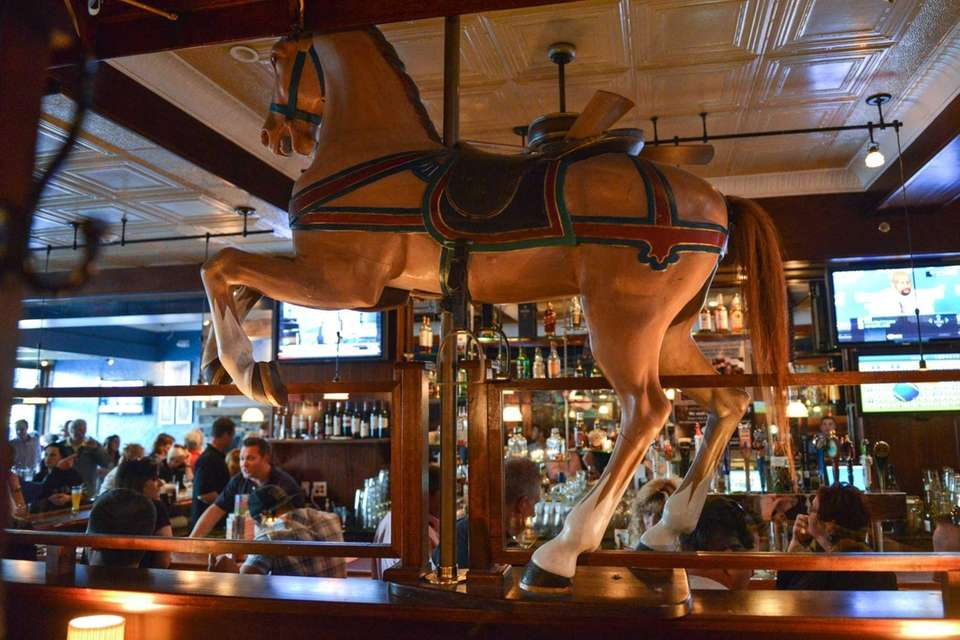 Old wooden merry-go-round horses line the booth seating