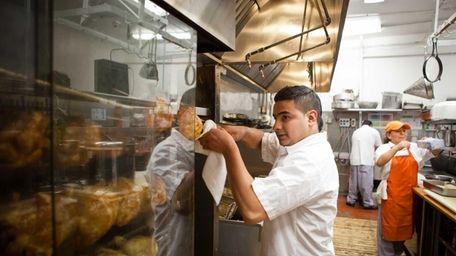 Gerver Guillen mans the rotisserie at Millennium Chicken