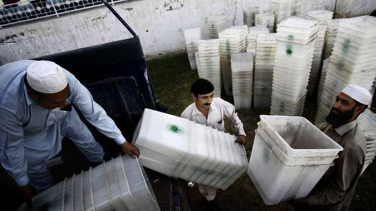 Pakistan Election Commission staff load ballot boxes on
