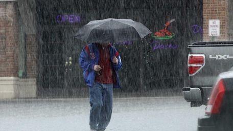 A man tries to avoid the rain as