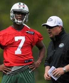 Jets quarterback Geno Smith, left, talks with offensive