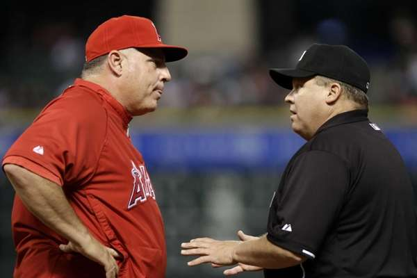 Los Angeles Angels manager Mike Scioscia, left, argues