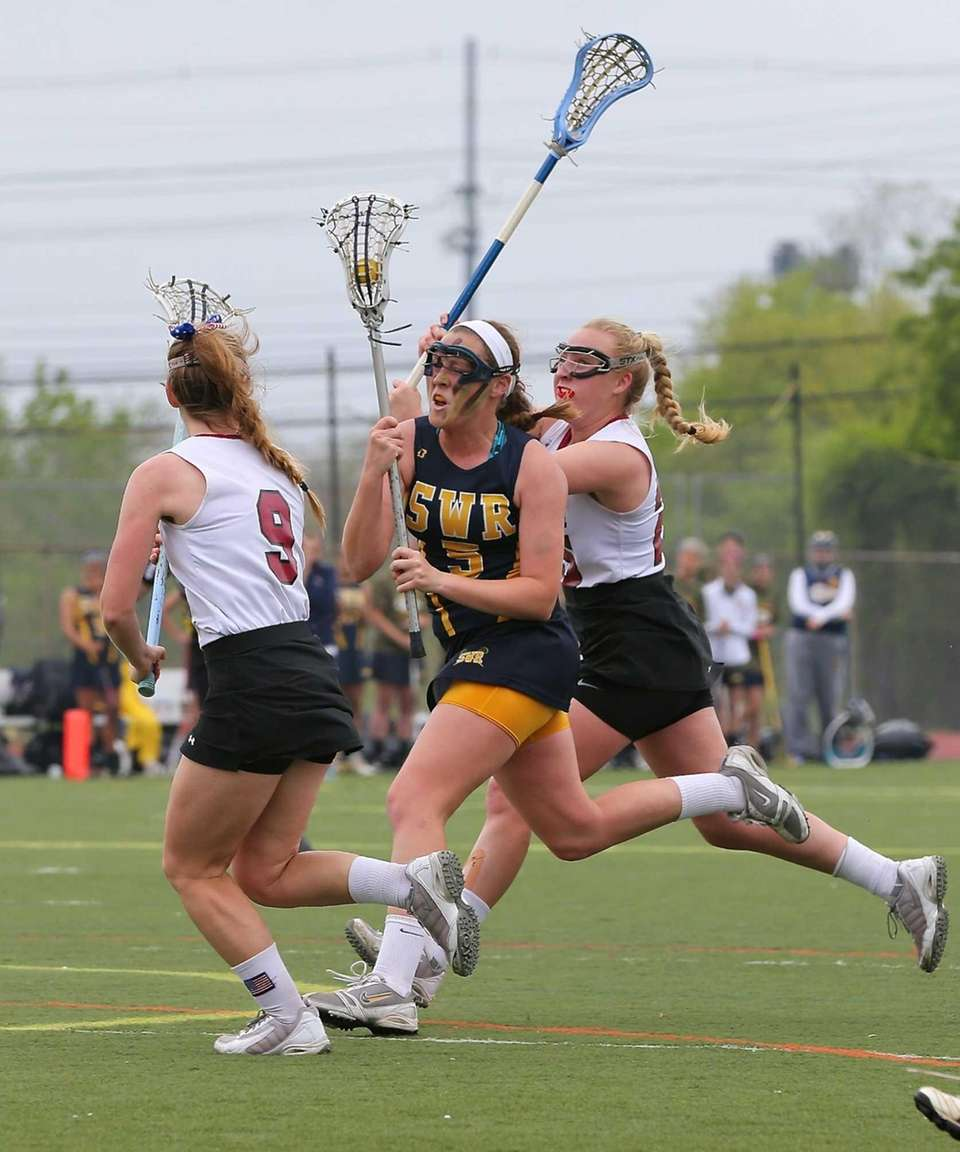 Shoreham's Jessica Angerman tries to stickhandle between two
