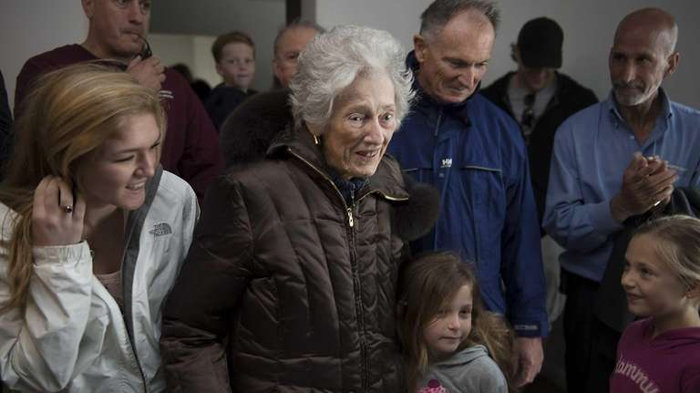 95-year-old Marie Clark, flanked by her family, returns