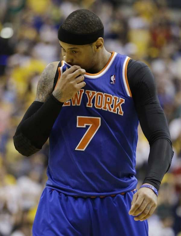 Carmelo Anthony wipes his face as he leaves