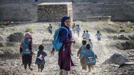 Afghan children run to school, September 2012. Khaled