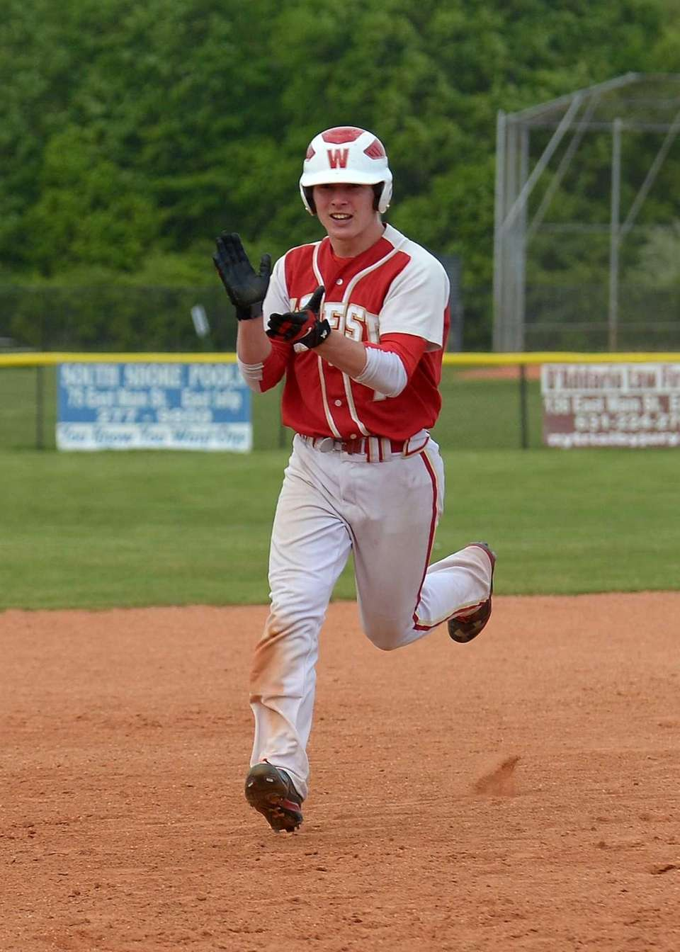 Hills West's David Golonowski (7) celebrates his two-run
