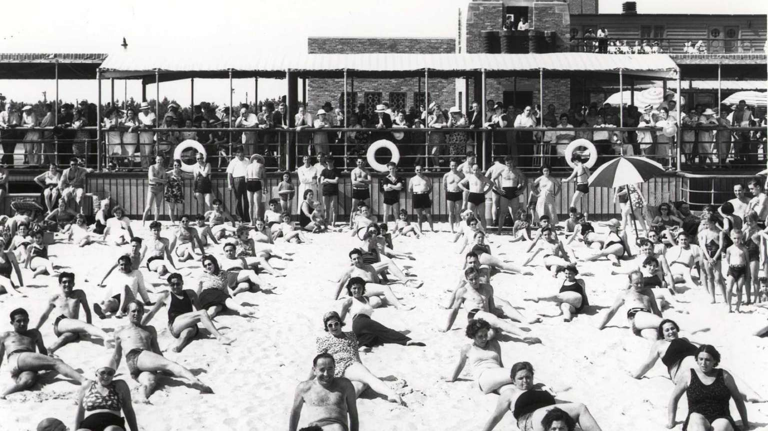 Beach-goers do coordinated exercises in the sand at