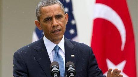 President Barack Obama speaks as a light rain