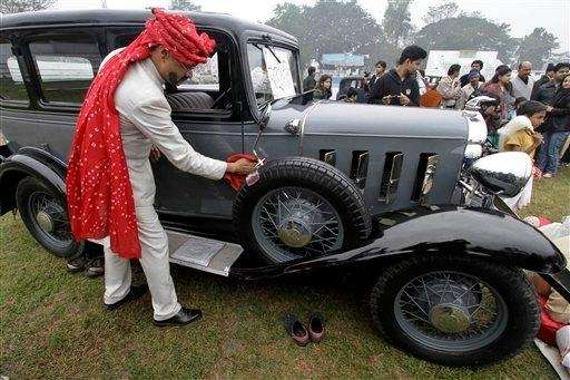 A participant dressed as chauffeur wipes his 1932