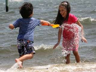 Danial Parveez, left, 4, plays in the water