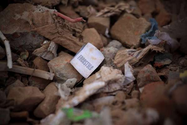 A clothing tag is seen amid rubble after
