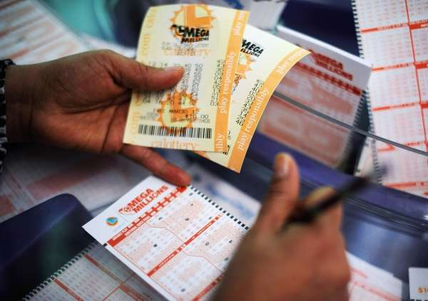A woman fills out a Mega Millions lottery