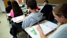 Students take notes during a lecture on May