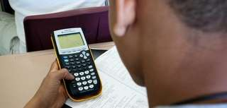 A student uses his calculator to solve math