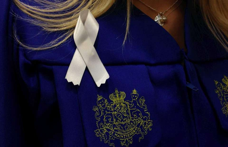 Hofstra University graduates wear white ribbons on their