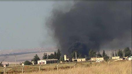 This citizen journalism image shows black smoke rising