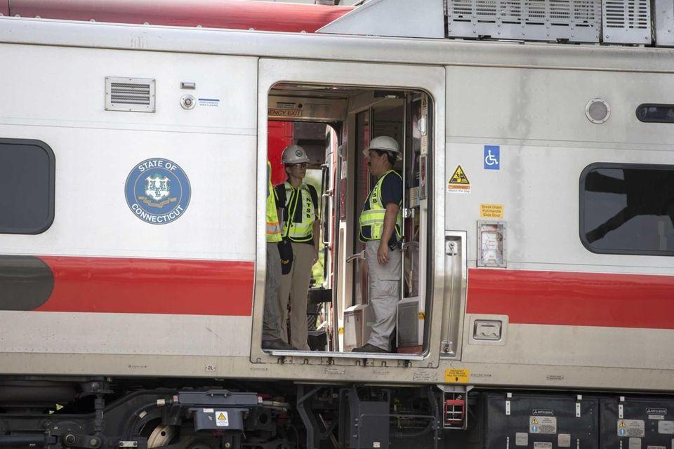 Investigators examine the scene of a Metro North