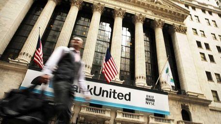 A man walks past the New York Stock