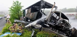 After a crash involving two trucks, firefighters extinguish a fire Monday morning that closed the eastbound Long Island Expressway at Exit 62, Blue Point Road, in Holtsville at 6:45 a.m., Suffolk County police said. (May 20, 2013)