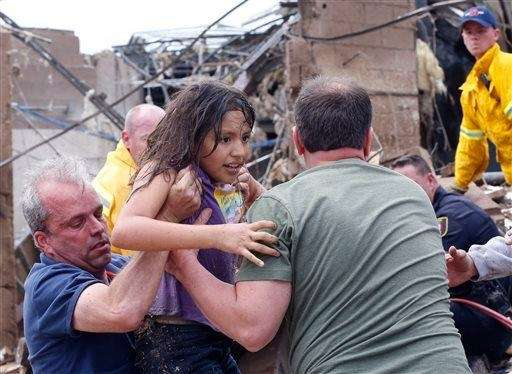 A child is pulled from the rubble of