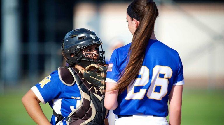 East Meadow catcher Kristen Arbiter (12) meets on
