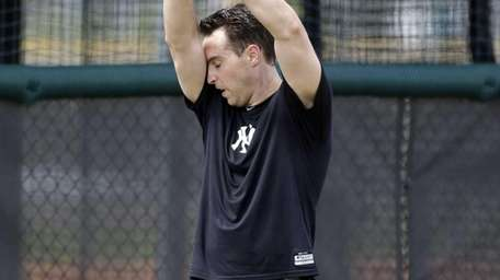 Mark Teixeira wipes his forehead during rehab workouts