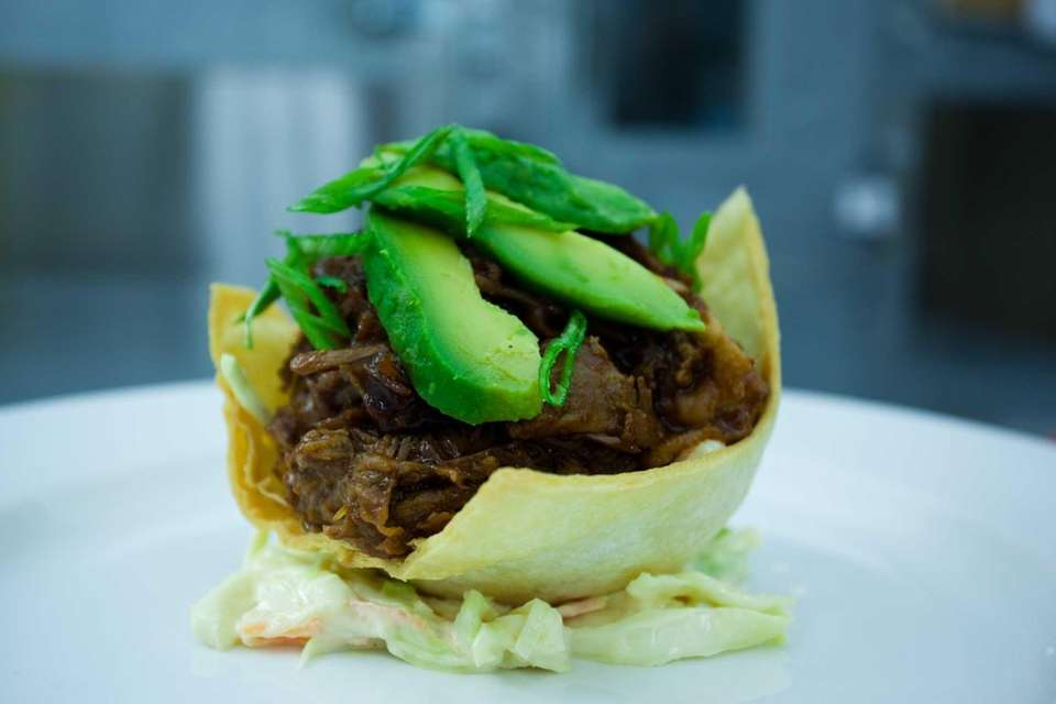 Bread & Butter's apple-braised, pulled-pork taco is garnished