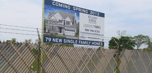 A sign announces a housing development for the